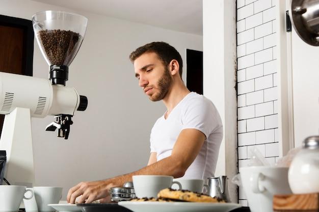 Mann barista, der hinter der theke arbeitet Kostenlose Fotos