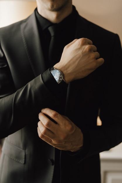 Mann befestigt einen manschettenknopf an seinem business-anzug Kostenlose Fotos