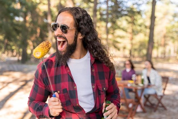 Mann beißt von einem gerösteten mais im freien Kostenlose Fotos