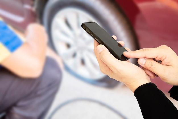 Mann benutzt handy anrufen jemand über reifenpannehintergrund des autos Kostenlose Fotos