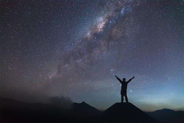 Mann breitet hand auf hügel aus und sieht die milchstraße Premium Fotos