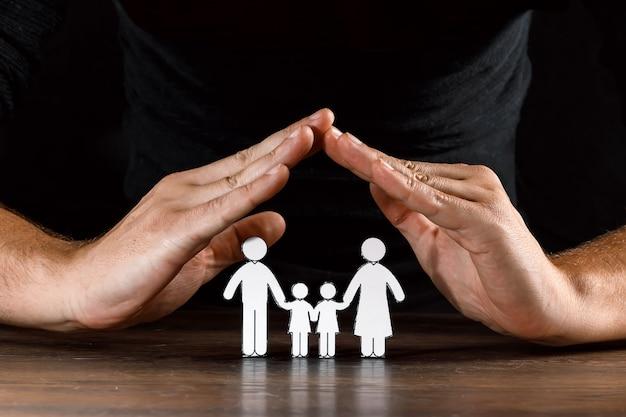 Mann deckt eine papierfamilie mit seinen händen ab Premium Fotos
