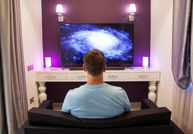 Mann, der 4k fernsehen aufpasst Premium Fotos