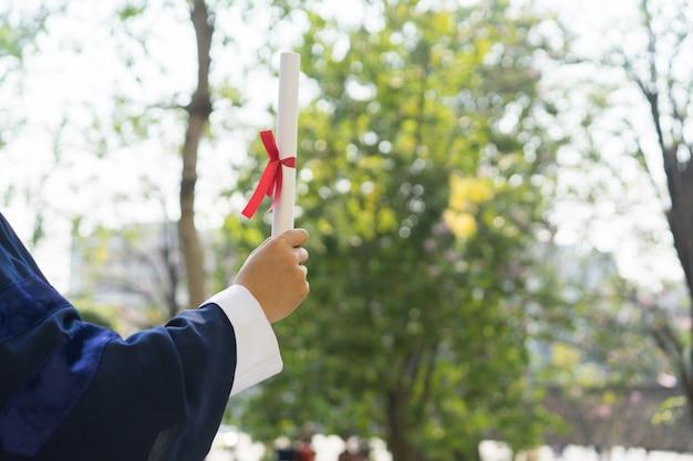 Mann, der abschluss-kleid trägt und zertifikatpapier mit mit band hält, nachdem er an der universität absolviert hat Premium Fotos