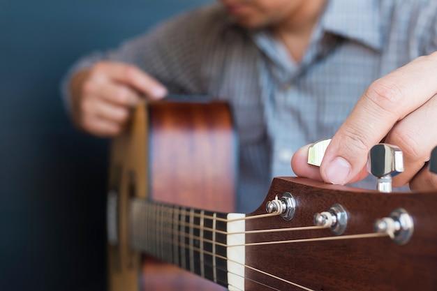 Mann, der akustische gitarre abstimmt Kostenlose Fotos