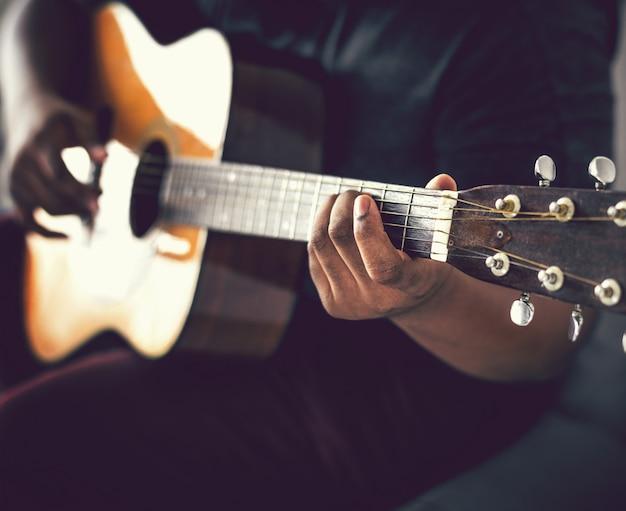 Mann, der allein eine akustische gitarre spielt Premium Fotos
