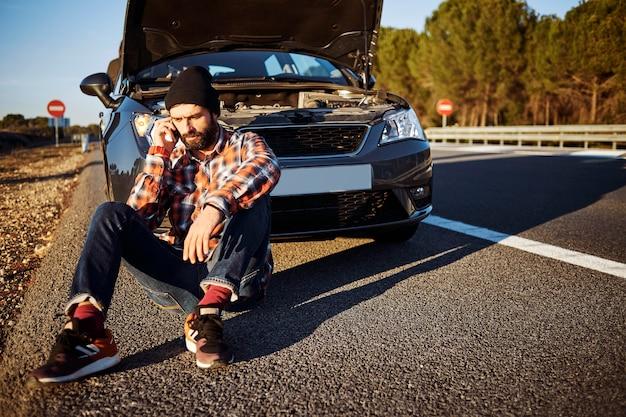 Mann, der am telefon neben auto spricht Kostenlose Fotos