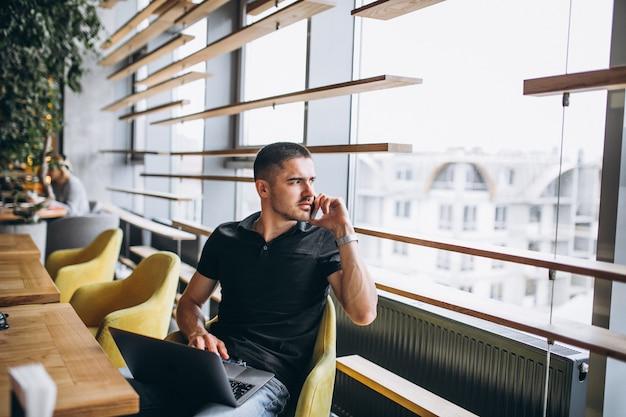 Mann, der am telefon sitzt in einem café spricht Kostenlose Fotos