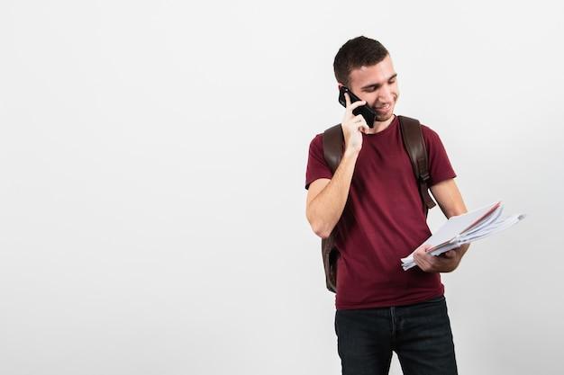 Mann, der am telefon spricht und seine anmerkungen betrachtet Kostenlose Fotos