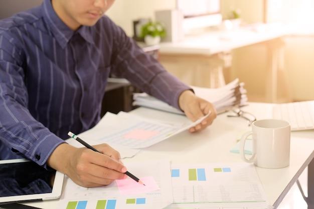 Mann, der an finanzdaten des tabellenkalkulationsdokuments, zugelassener wirtschaftsprüfer arbeitet. Premium Fotos