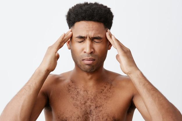 Mann, der an migräne leidet, schläft nur für einige stunden und bereitet sich auf abschlussprüfungen in der universität vor. junger mann, der ohne kleidung vor dem spiegel steht und morgens mit den händen den kopf drückt. Kostenlose Fotos