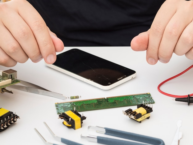 Mann, der an seinem arbeitstisch mit elektronik sitzt Kostenlose Fotos