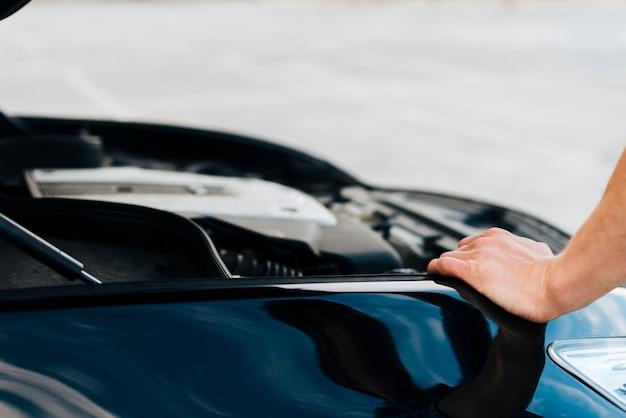 Mann, der auf auto mit offener haube sich lehnt Kostenlose Fotos