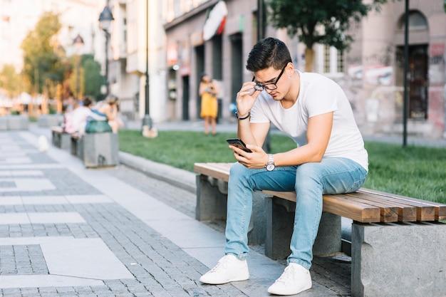 Mann, der auf bank unter verwendung des handys sitzt Kostenlose Fotos