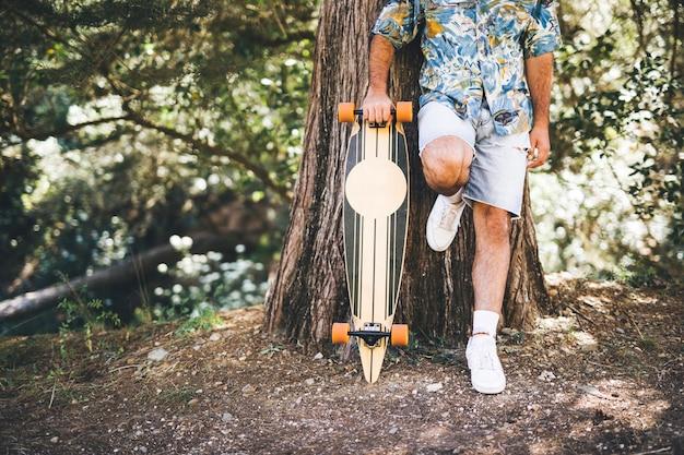 Mann, der auf baum mit skateboard sich lehnt Kostenlose Fotos