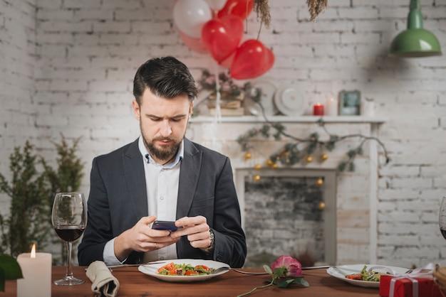 Mann, der auf datum wartet, telefon überprüfend Kostenlose Fotos