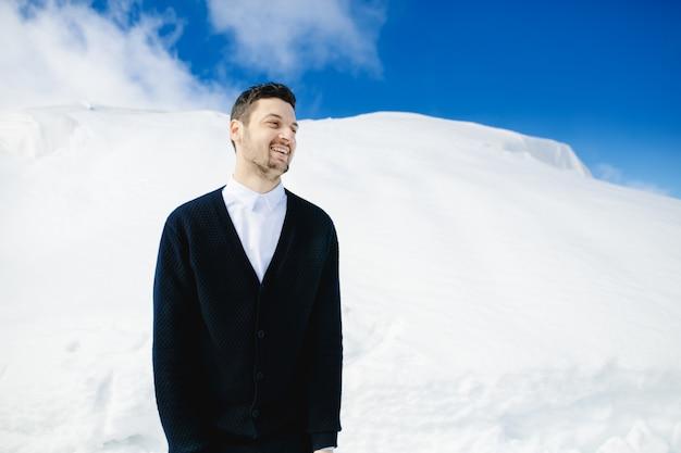 Mann, der auf dem abhang des schneebedeckten berges steht Kostenlose Fotos