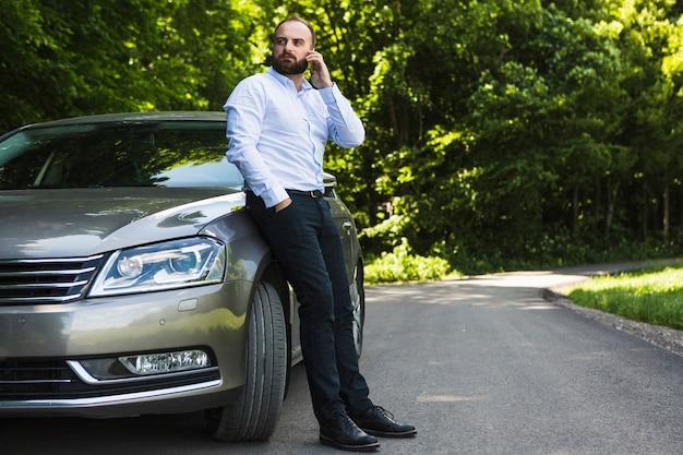 Mann, der auf dem auto spricht auf smartphone sich lehnt Kostenlose Fotos