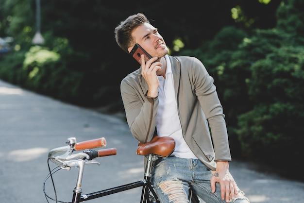 Mann, der auf dem fahrrad spricht am handy sitzt Kostenlose Fotos