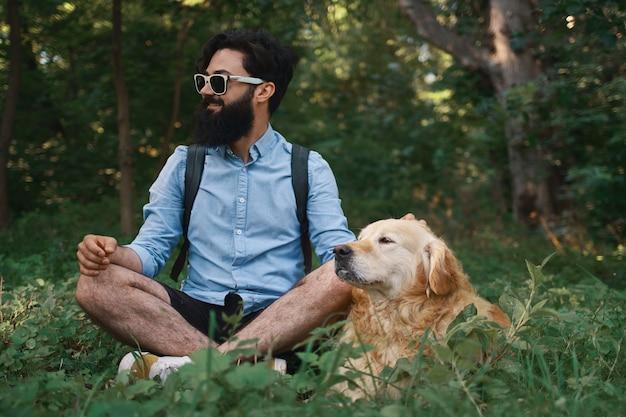 Mann, der auf dem gras ruht, das gekreuzte beine mit seinem hund sitzt Kostenlose Fotos