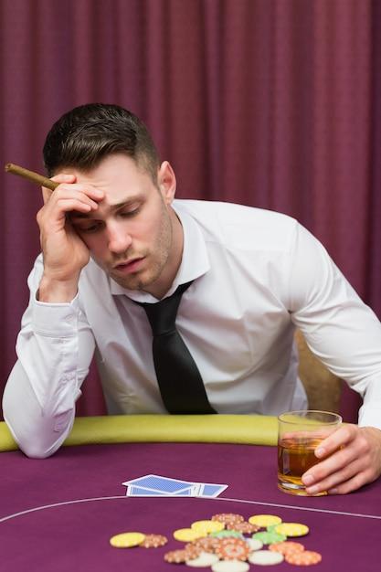 Mann, der auf dem pokertisch anhält zigarre sich lehnt Premium Fotos