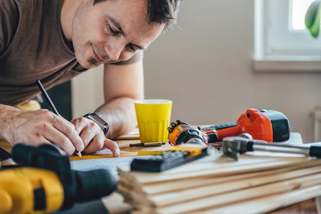 Mann, der auf dem tisch entwurfsplan mit bleistift macht Premium Fotos