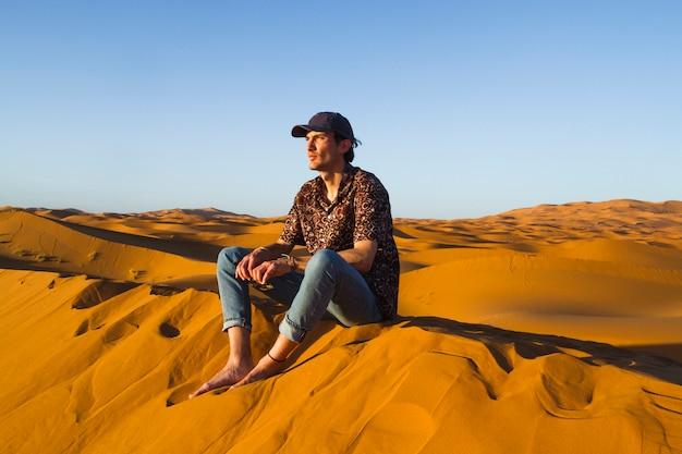 Mann, der auf düne in der wüste sitzt Kostenlose Fotos