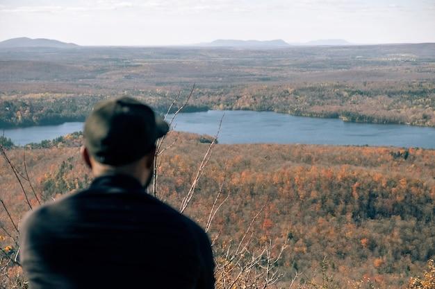 Mann, der auf einem berg mit einem schönen blick auf fluss und ebenen ruht Kostenlose Fotos