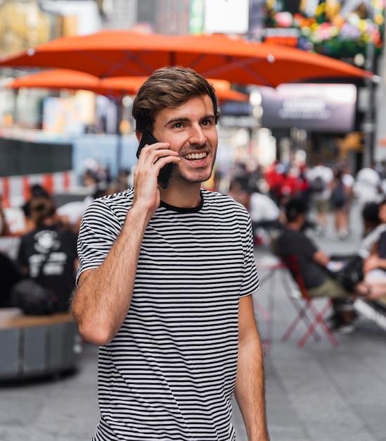 Mann, der auf einem smartphone vor einer terrasse spricht Kostenlose Fotos