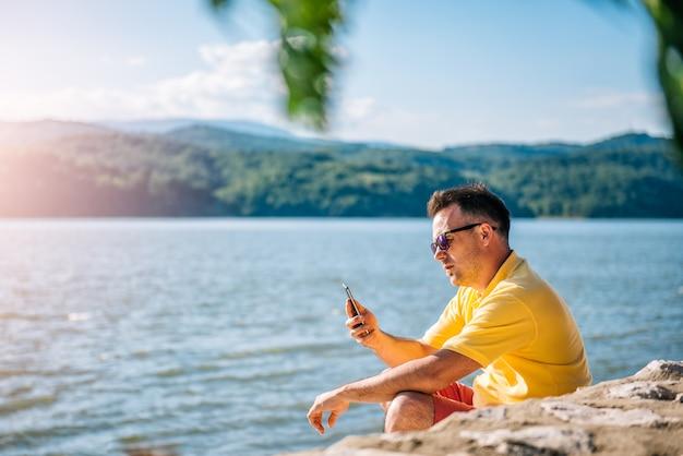 Mann, der auf einem strand sitzt und intelligentes telefon verwendet Premium Fotos