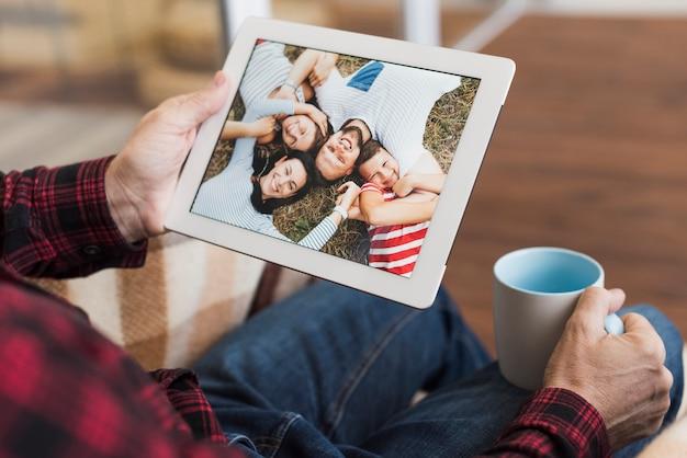 Mann, der auf fotos mit seinen kindern und enkelkindern schaut Kostenlose Fotos