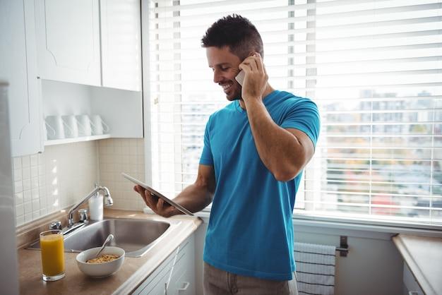 Mann, der auf handy spricht, während digitales tablett in küche verwendet wird Kostenlose Fotos