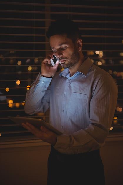 Mann, der auf handy spricht, während digitales tablett verwendet wird Kostenlose Fotos