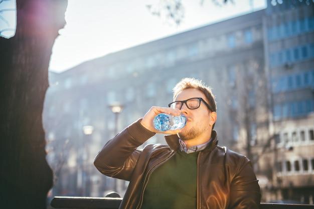 Mann, der auf parkbank und trinkwasser sitzt Premium Fotos
