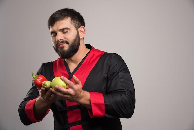 Mann, der auf rotem pfeffer, apfel und zucchini schaut. Kostenlose Fotos