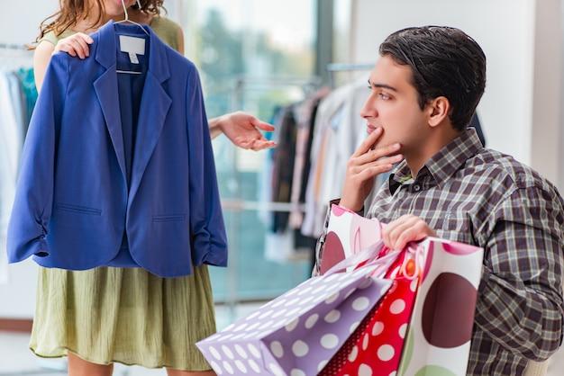 Mann, der auf seine frau während des weihnachtseinkaufs wartet Premium Fotos