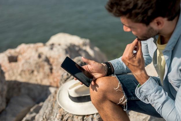 Mann, der auf smartphone küste betrachtet Kostenlose Fotos