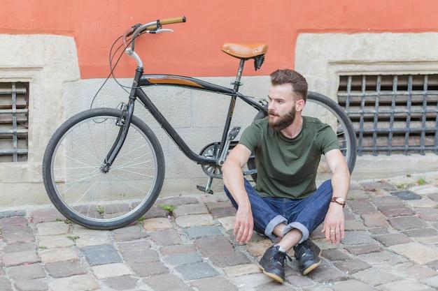 Mann, der auf steinpflasterung vor fahrrad sitzt Kostenlose Fotos