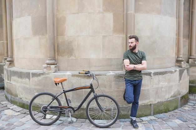 Mann, der auf wand nahe bei seinem fahrrad sich lehnt Kostenlose Fotos