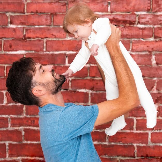 Mann, der baby mit ziegelsteinhintergrund hält Kostenlose Fotos