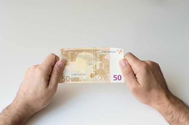 Mann, der banknote des euros fünfzig in seinen händen hält Premium Fotos