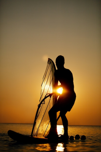 Mann, der bei sonnenuntergang sailboarding ist Premium Fotos