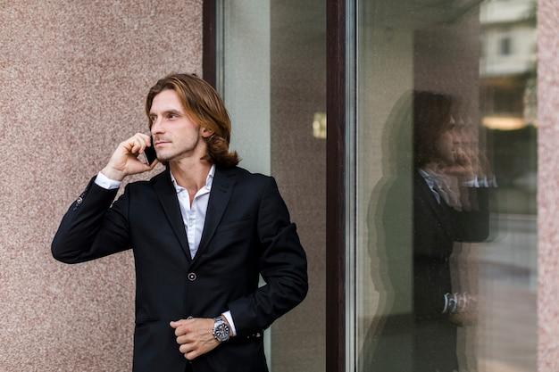 Mann, der beim sprechen am telefon weg schaut Kostenlose Fotos