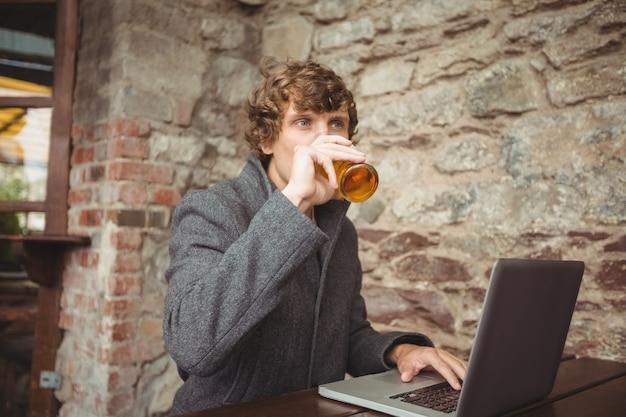 Mann, der bier beim verwenden des laptops hat Kostenlose Fotos
