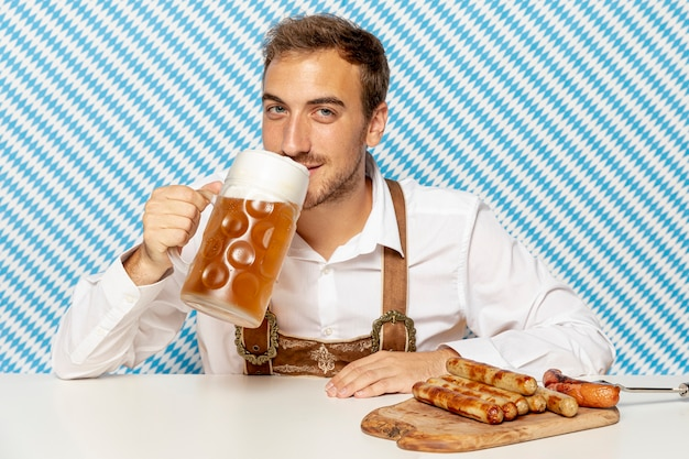 Mann, der blondes bier und deutsche würste trinkt Kostenlose Fotos