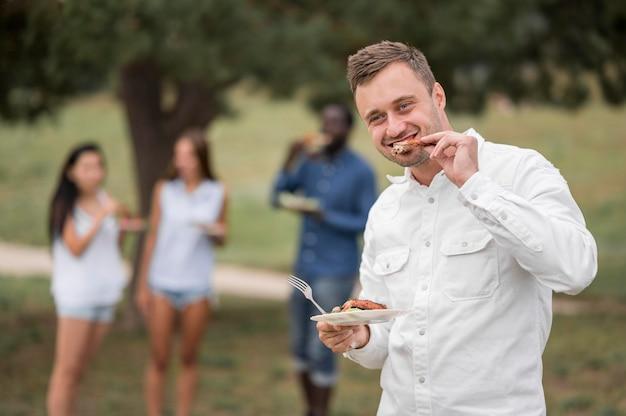 Mann, der das essen an einem grill genießt Kostenlose Fotos