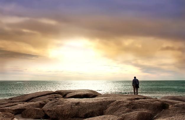 Mann, der das meer steht auf seesteinen gegenüberstellt Premium Fotos