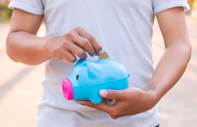 Mann, der das sparschwein, geldkonzept sparend hält. Premium Fotos