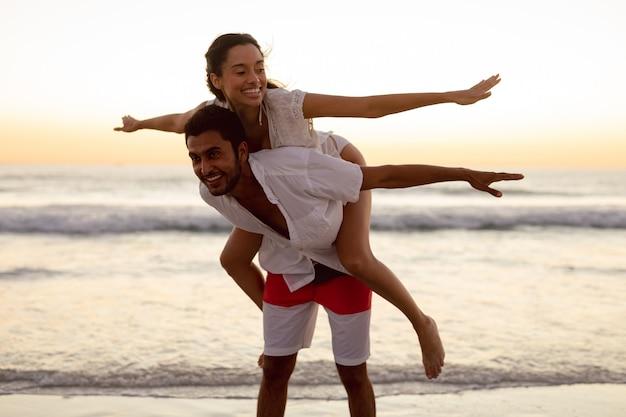 Mann, der der frau auf dem strand doppelpolfahrt gibt Kostenlose Fotos