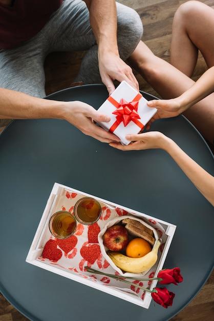 Mann, der der frau kleine geschenkbox gibt Kostenlose Fotos